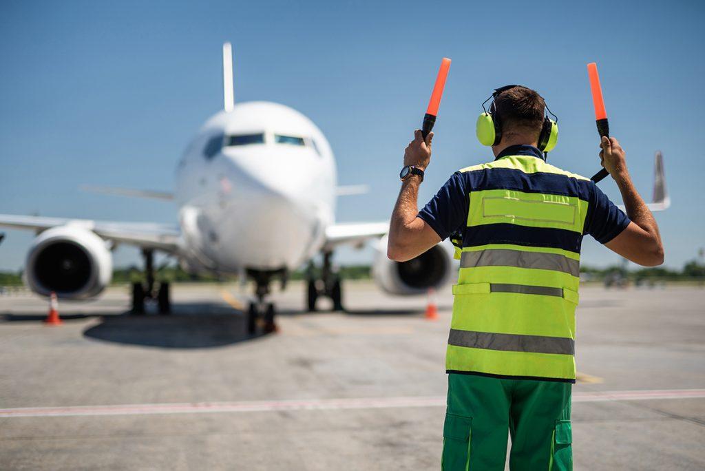 Airport worker in headphones meeting passenger plane